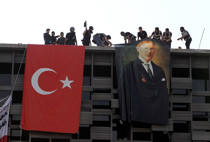 Police hang a banner of Mustafa Kemal Ataturk, founder of modern Turkey, next to a Turkish flag hung by protesters in a cultural center during a police operation to clear Taksim Square in Istanbul on Tuesday, June 11, 2013. Hundreds of police in riot gear forced through barricades and pushed many of the protesters who had occupied the square for more than a week into a nearby park. (AP Photo/Thanassis Stavrakis)