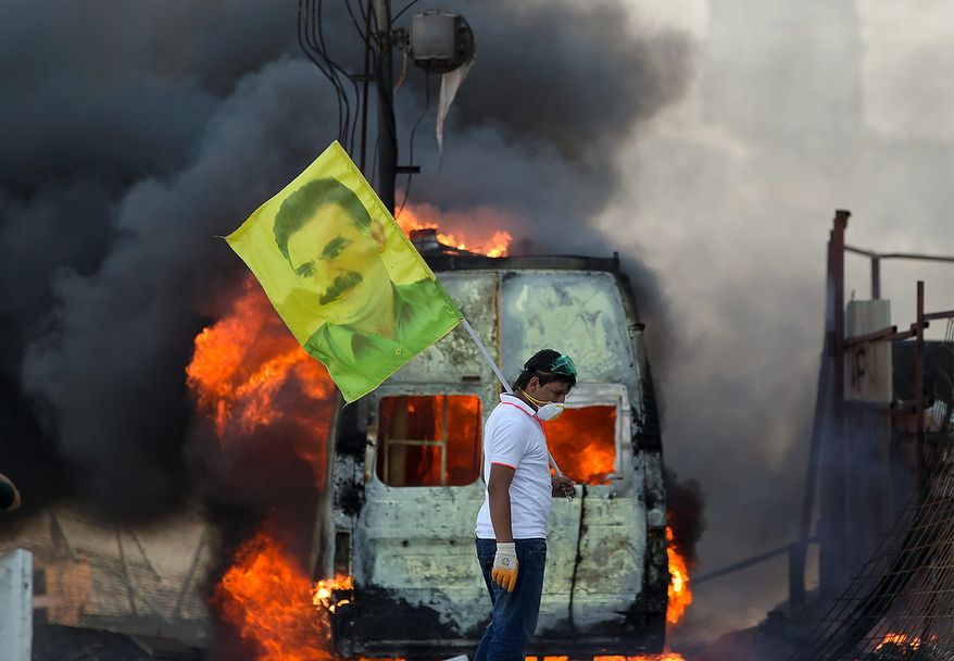 A protester holds a flag depicting jailed Kurdish rebel leader Abdullah Ocalan as a van burns during clashes in Taksim Square in Istanbul on Tuesday, June 11, 2013. Hundreds of riot police overran improvised barricades on the square and fired tear gas, rubber bullets and water cannon in running battles with protesters who have been occupying the area for more than a week. (AP Photo/Vadim Ghirda)