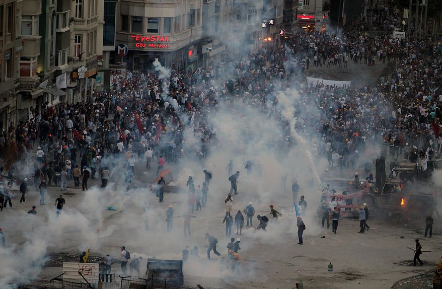 Police throw tear gas at protesters during clashes on Taksim Square in Istanbul on Tuesday, June 11, 2013. Riot police were re-entering the plaza after defiant protesters swarmed back in by the thousands. Massive plumes of tear gas billowed upward, and police fired water cannon. (AP Photo/Thanassis Stavrakis)