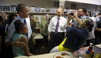 Sean and Natalie Guthrie, of Boston, right, take photos of their 11-year-old daughter Leilani Guthrie posing with President Barack Obama, as he and Massachusetts Democratic Senate candidate, Rep. Ed Markey watch at center during a campaign stop at Charlie's Sandwich Shoppe in Boston, Wednesday, June 12, 2013. (AP Photo/Evan Vucci)