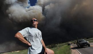Dave Dunlap watches from the bed of his truck as a wildfire crosses Black Forest Road near his home Tuesday afternoon, June 11, 2013, in Colorado Springs, Colo. The Black Forest Fire was one of at least three significant wildfires burning in Colorado amid gusty winds and record-breaking hot, dry weather. (AP Photo/The Colorado Springs Gazette, Christian Murdock)
