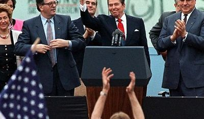 "** FILE ** A spectator jumps up as President Reagan gives a thumbs up sign after his speech in front of the Brandenburg Gate in West Berlin, where he said ""Mr. Gorbachev, tear down this wall."" (Associated Press)"