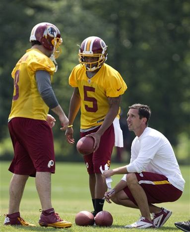 Washington Redskins' offensive coordinator Kyle Shanahan, right, talks with quarterbacks Rex Grossman (8) and Pat White (5) during NFL football minicamp at Redskins Park, Wednesday, June 12, 2013, in Ashburn, Va. (AP Photo/Carolyn Kaster)
