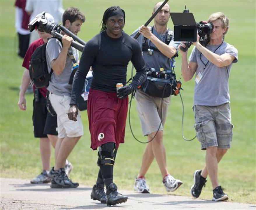 Washington Redskins' quarterback Robert Griffin III is followed by a camera crew during an NFL football minicamp at Redskins Park, Wednesday, June 12, 2013, in Ashburn, Va. Griffin wears a knee brace as he works to recover from surgery to repair his ACL, LCL and meniscus. (AP Photo/Carolyn Kaster)