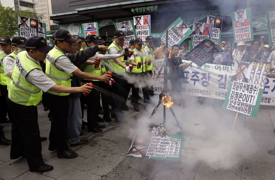 South Korean police officers spray fire extinguishers after protesters burnt an effigy of North Korean leader Kim Jong Un and its flag during an anti-North Korea rally denouncing the cancellation of Koreas high-level talks in downtown Seoul on June 12, 2013. (Associated Press)