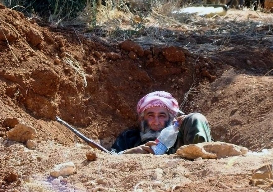 This citizen journalism image provided by Edlib News Network, ENN, which has been authenticated based on its contents and other AP reporting, shows an elderly Syrian rebel sitting in a trench, in Idlib province, northern Syria, Wednesday, June 12, 2013. Syrian rebels have attacked a village in the country's east, killing dozens of Shiites, mostly pro-government fighters, activists said Wednesday. (AP Photo/Edlib News Network ENN)