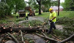 Scott Edwards with Montgomery County Highway helps clean up fallen trees in the Cloverly neighborhood after severe storms came through the region bringing heavy rain and winds, Silver Spring, Md., Thursday, June 13, 2013. (Andrew Harnik/The Washington Times)