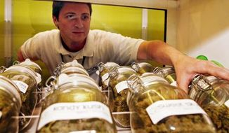 A man reaches for a jar of medical marijuana at a Denver clinic. (Associated Press)