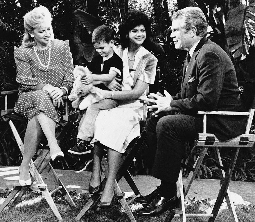 Laura Walker Snyder (center) holds her son Christopher while talking to Pat Robertson (right) and Danuta Sodermah on Monday, June 18, 1985 in Los Angeles. Robertson and Sodermah were interviewing Walker Snyder, one of the four children of John A. Walker Jr., who is charged with espionage, for the Christian Broadcasting Network?s 700 Club program to be aired at a later date. (AP Photo/Linda C. Culpepper)