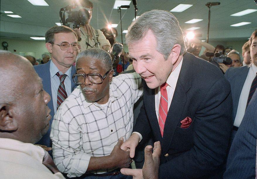 Republican presidential candidate Pat Robertson, right, shakes hands as he meets supporters at the Allapattah Community Center in Miami, Florida, Feb. 29, 1988. Robertson was spending the day campaigning in the Miami area making stops at the community center, La Salle Catholic High School and taking time to open his Miami campaign headquarters. (AP Photo/Chris O'Meara)