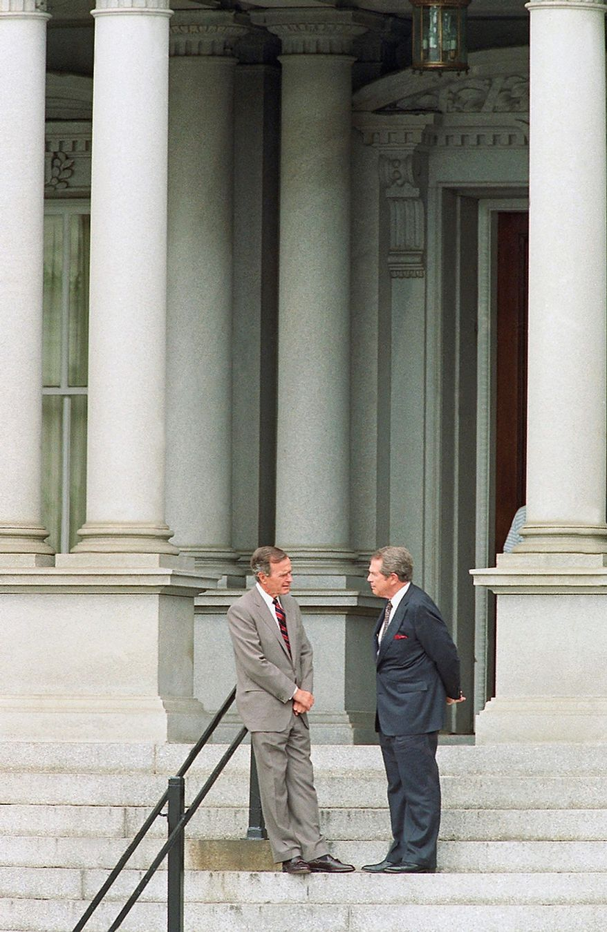 U.S. President George H. Bush, left, stops to chat with evangelist Pat Robertson on the stops of the Old Executive Office Building in Washington, Thursday, July 23, 1992. Bush was at the Old Executive Office Building, located next to the White House, to tape an interview with Robertson. (AP Photo/Doug Mills)