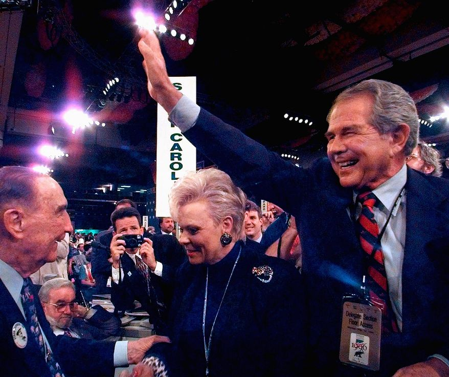 Pat Robertson, right, founder of the Christian Coalition, waves to the crowd as he is joined by South Carolina Senator Strom Thurmond, left, on the floor of the Republican National Convention, Monday, Aug. 12, 1996 in San Diego. Woman in center is unidentified. (AP Photo/Ruth Fremson)