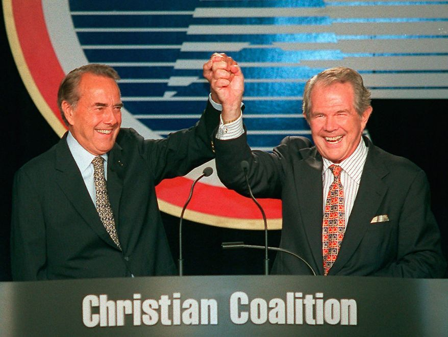 "Republican presidential candidate Bob Dole and Christian Coalition founder Pat Robertson clasp hands after Robertson introduced Dole at the Christian Coalition convention in Washington Saturday, Sept. 14, 1996. Earlier in the morning, Robertson told his roup's annual convention it will take ""a miracle from Almighty God"" for Dole to win the presidency. (AP Photo/Mark Wilson)"