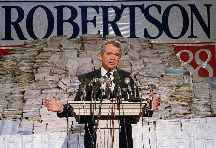 Pat Robertson, stands in front of stacks of signatures as he announced his intentions to collect a total of 7 million signatures during a news conference on Tuesday, Sept. 15, 1987 in Chesapeake, Virginia. Robertson also announced that he will make a formal announcement about his Presidential plans on Oct. 1. (AP Photo/Steve Helber)