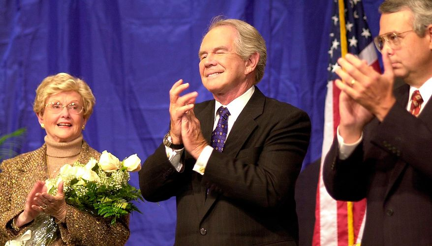 """Pat Robertson, center, the founder of the Christian Broadcasting Network,  his wife, Adelia """"Dede"""" Robertson, left, and Michael D. Little, right, the president and chief operating officer of CBN, applaud during celebrations marking the 40th anniversary of the on the air debut of the network.  (AP Photo/Gary C. Knapp)"""