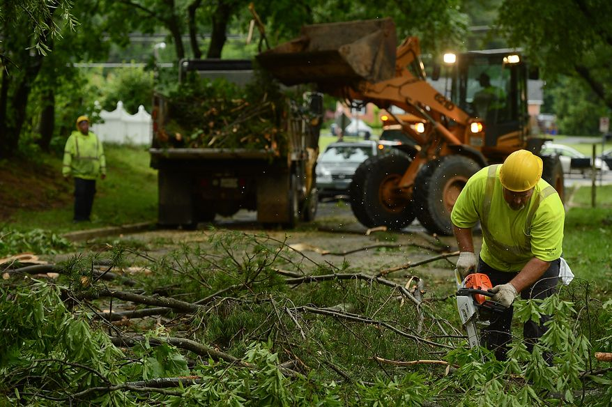 Scott Edwards with Montgomery County Highway, right, helps a crew clean up fallen trees in the Cloverly neighborhood after severe storms came through the region bringing heavy rain and winds, Silver Spring, Md., Thursday, June 13, 2013. (Andrew Harnik/The Washington Times)
