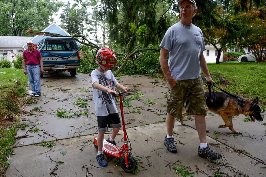 Steve Roper and his son Ely, 9, bring their dog, Maverick, out with them as they check in on Jose Torres, left, who sustained damage to his truck from a large branch which fell outside his house in the Cloverly neighborhood after severe storms came through the region bringing heavy rain and winds, Silver Spring, Md., Thursday, June 13, 2013. (Andrew Harnik/The Washington Times)