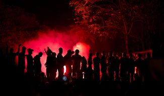 Protesters chant anti-government slogans, silhouetted by the light of flares in Taksim square, in Istanbul, Turkey, late Wednesday, June 12, 2013. (AP Photo/Vadim Ghirda)