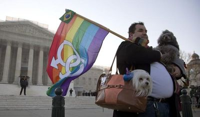 **FILE** Marcos German Domingues of Massachusetts stands with his dogs Sophia (left) and Georg in front of the Supreme Court in Washington on March 27, 2013. (Associated Press)