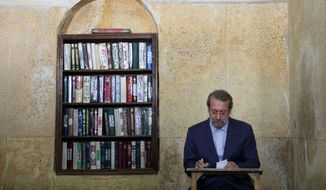 Iran's Parliament speaker Ali Larijani attends a polling station during presidential elections in Qom, 125 kilometers (78 miles) south of the capital Tehran, Iran, Friday, June 14, 2013. (AP Photo/Ebrahim Noroozi)