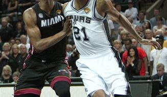 Miami Heat forward Chris Bosh,left, battle for a lose ball against San Antonio forward Tim Duncan during the fourth quarter of Game 4 in the NBA Finals between the Miami Heat against the San Antonio Spurs at the At&t Center in San Antonio on Thursday, June 13, 2013. Riding big performances from their three All-Stars, the Heat tied the NBA Finals with a 109-93 victory over the San Antonio Spurs on Thursday night in Game 4. (AP Photo/El Nuevo Herald, David Santiago)