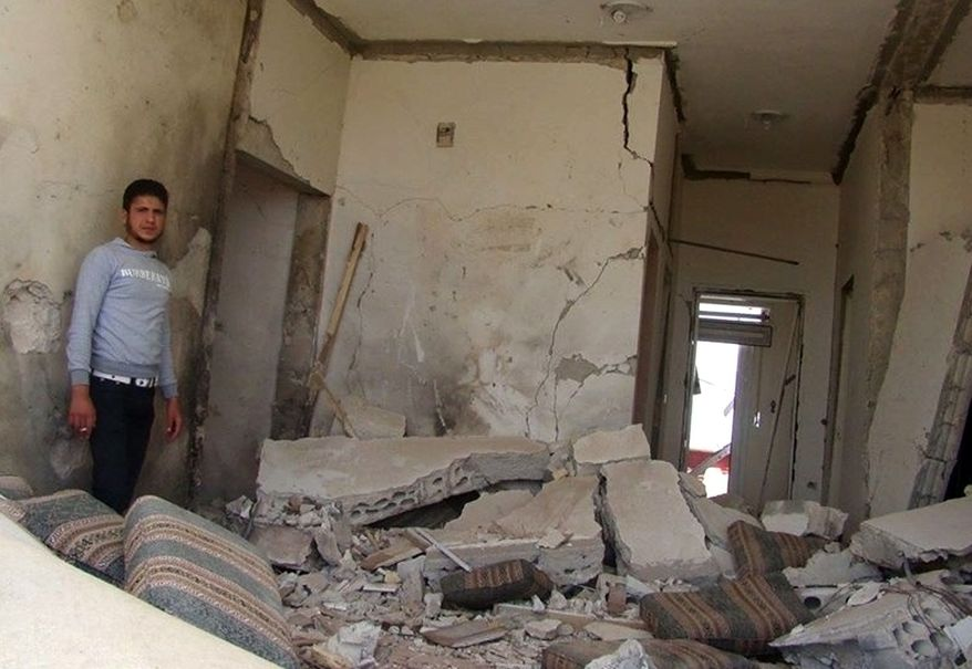 This citizen journalism image provided by Edlib News Network, ENN, which has been authenticated based on its contents and other AP reporting, shows a Syrian man checking his destroyed house that was damaged by a Syrian forces air strike, in Idlib province, northern Syria, Thursday, June 13, 2013. (AP Photo/Edlib News Network ENN)
