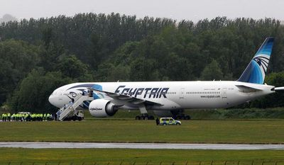 Passengers leave an Egyptair aircraft at Glasgow Prestwick Airport in Scotland after it was diverted while en route from Cairo to New York on Saturday, June 15, 2013. It is reported that BBC employee Nada Tafik, who was on board the plane, said she found a note in a toilet apparently threatening to start a fire. The plane was escorted to Prestwick by Typhoon fighters from RAF Leuchars, near St. Andrews on the east coast of Scotland. (AP Photo/Andrew Milligan, Press Association)