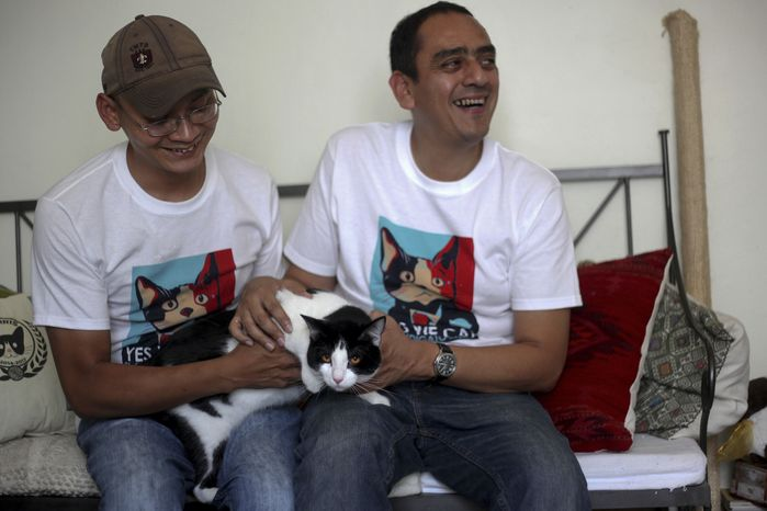 "Diego Cruz (left) and Sergio Chamorro pose with their cat, Morris, in their home in Xalapa, Mexico, on Saturday, June 15, 2013. Put forth as candidate by Mr. Camacho and a group of friends after they became disillusioned with the empty promises of politicians, Morris, a black-and-white cat with orange eyes, is running for mayor of Xalapa, in eastern Mexico, with the campaign slogan ""Tired of Voting for Rats? Vote for a Cat."" And he is attracting tens of thousands of politician-weary, two-legged supporters on social media. (AP Photo/Felix Marquez)"