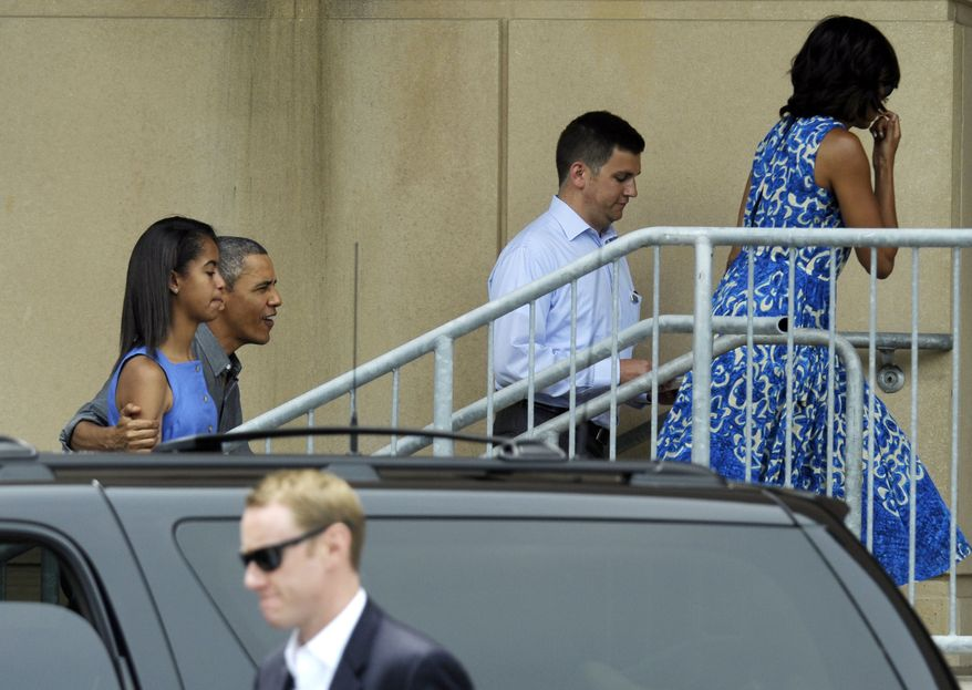 President Obama, with his arm around daughter Malia, and first lady Michelle Obama (right) arrive at the Music Center at Strathmore in North Bethesda, Md., on Sunday, June 16, 2013, to attend daughter Sasha's dance recital. (AP Photo/Susan Walsh)