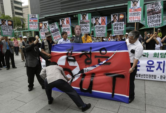 Protesters cut up a North Korean flag during an anti-North Korea rally in downtown Seoul on Wednesday, June 12, 2013, to denounce the cancellation of the Koreas' high-level talks, which were scrapped a day before they were to begin Wednesday because the sides didn't agree on the delegation leaders, South Korea said. (AP Photo/Lee Jin-man)