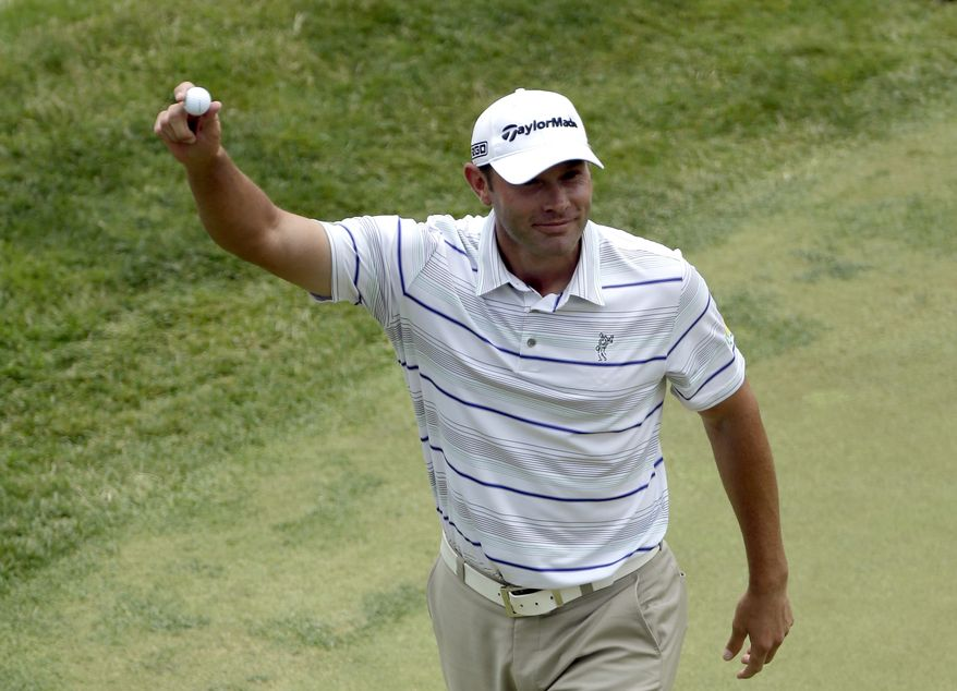 Shawn Stefani shows off the ball to the gallery after hitting a hole in one on the 17th hole during the fourth round of the U.S. Open golf tournament at Merion Golf Club, Sunday, June 16, 2013, in Ardmore, Pa. (AP Photo/Julio Cortez)