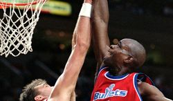 **FILE** Washington Bullets forward Chris Webber, right, goes for the stuff shot over Portland Trail Blazers center Arvydas Sabonis during NBA action in Portland, Ore., Monday, Dec. 23, 1996. The Bullets changed their name to the Wizards given the violent connotation. (AP Photo/Don Ryan)