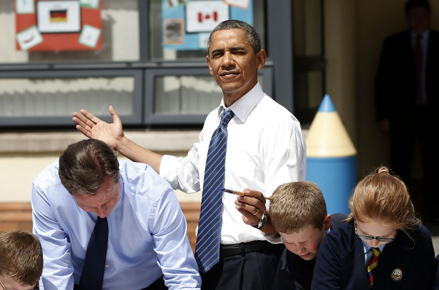 ** FILE ** President Obama (center) reacts as the sun comes out as he and British Prime Minister David Cameron (left) help students as they work on a school project about the G-8 summit during a visit to the Enniskillen Integrated Primary School in Enniskillen, Northern Ireland, on June 17, 2013. The visit took place before leaders from the G-8 nations were to gather to discuss the ongoing conflict in Syria and free-trade issues. (Associated Press)