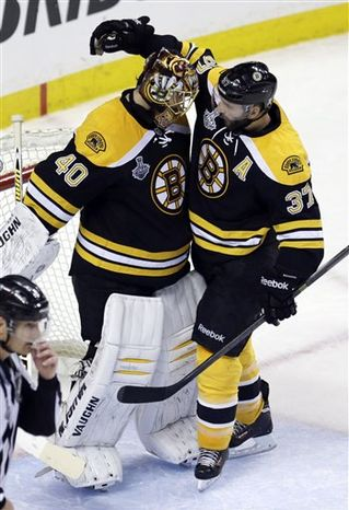 Boston Bruins center Patrice Bergeron (37) congratulates Boston Bruins goalie Tuukka Rask (40), of Finland, on his shutout after the Bruins beat the Chicago Blackhawks 2-0 in Game 3 of the NHL hockey Stanley Cup Finals in Boston, Monday, June 17, 2013. (AP Photo/Charles Krupa)