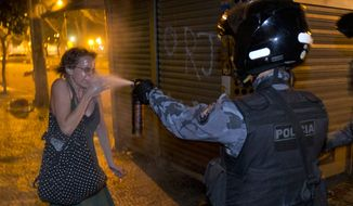 **FILE** A military police officer pepper-sprays a protester during a demonstration in Rio de Janeiro on June 17, 2013. Protesters massed in at least seven Brazilian cities for another round of demonstrations voicing disgruntlement about life in the country, raising questions about security during big events such as the ongoing Confederations Cup and a papal visit the following month. (Associated Press)