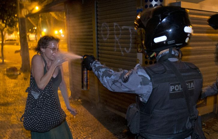 **FILE** A military police officer pepper-sprays a protester during a demonstration in Rio de Janeiro on June 17, 2013. Protesters massed in at least seven Brazilian cities for another round of demonstrations voicing disgruntlement about life in the c