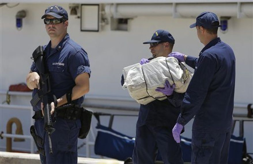 ** FILE ** Coast Guard crew members from the cutter Bernard C. Webber offload bales of cocaine, Friday, April 26, 2013 at the U.S. Coast Guard base in Miami Beach, Fla. The 2,200 pounds of cocaine, worth an estimated $27 million, was seized after stopping a fishing boat in the Western Caribbean Sea. (Associated Press)