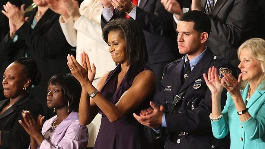 ** FILE ** Rirchard DeCoatsworth sits with first lady Michelle Obama at the president's State of the Union speech in 2009. (Associated Press)