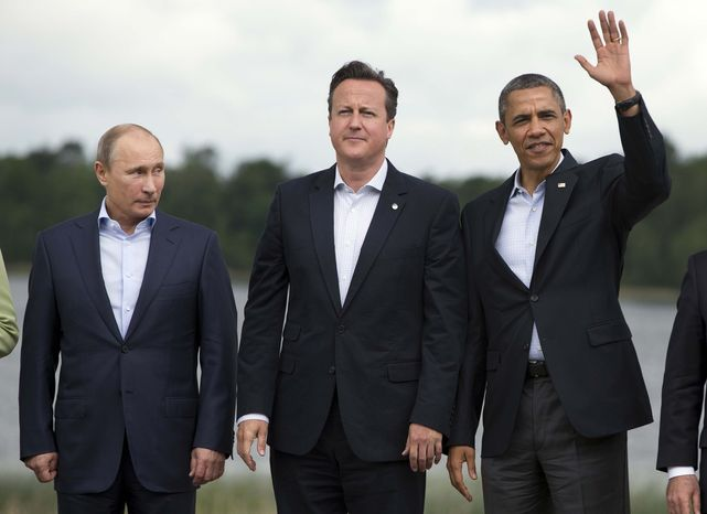 Russian President Vladimir Putin, left, looks toward British Prime Minister David Cameron, center, and U.S. President Barack Obama during group photo with G-8 leaders on Tuesday, June 18, 2013, in Enniskillen, Northern Ireland. (AP Photo/Evan Vucci)