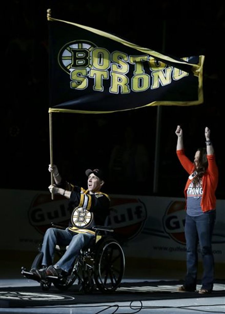 """Richard Donohue, the Massachusetts Bay Transportation Authority officer wounded during the shootout with the Boston Marathon bombing suspects, waves a """"Boston Strong"""" banner as his wife, Kimberly, raises her arms during ceremonies prior to Game 3 of the Eastern Conference finals in the NHL hockey Stanley Cup playoffs between the Boston Bruins and the Pittsburgh Penguins, in Boston on Wednesday, June 5, 2013. (AP Photo/Elise Amendola)"""