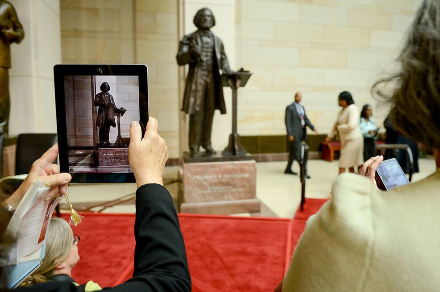 Visitors take a photographs of a statue of Frederick Douglass before a congressional ceremony to commemorate the dedication and unveiling of the statue in Emancipation Hall of the the United States Visitors Center, Washington, D.C., Wednesday, June 19, 2013. (Andrew Harnik/The Washington Times)