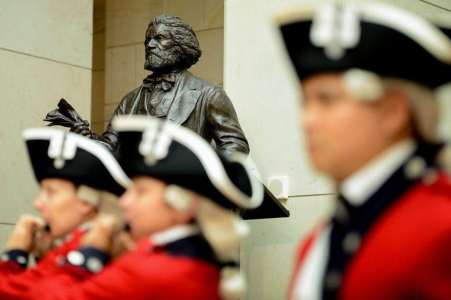 Colonial soldiers in red regimental uniform perform at a congressional ceremony to commemorate the dedication and unveiling of a statue of Frederick Douglass in Emancipation Hall of the the United States Visitors Center, Washington, D.C., Wednesday, June 19, 2013. (Andrew Harnik/The Washington Times)
