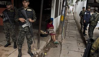 In this June 1, 2013, photo, a female member of the Honduras National Police takes part in a patrol with Honduras Army soldiers in a market of the John F. Kennedy neighborhood in Tegucigalpa, Honduras. (AP Photo/Esteban Felix)