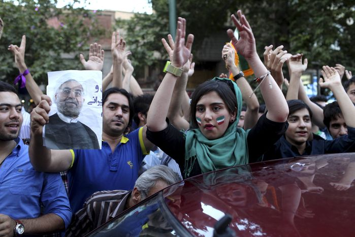 Iranians attend a street celebration, in Tehran, after their national soccer team qualified for the Brazil 2014 World Cup, after defeating South Korea, as one of them holds a poster of President-elect Hasan Rowhani, on Tuesday, June 18, 2013. The win set off wild celebrations across Iran, where the government had given a rare approval for supporters to spill into the streets. (AP Photo/Ebrahim Noroozi)