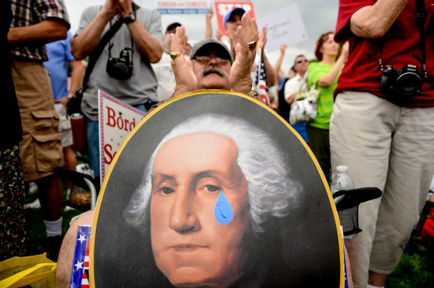 """David Grimm of Pittsburgh holds a poster depicting a crying George Washington as he applauds for speakers during """"Audit the IRS,"""" a tea party rally against the Internal Revenue Service on the West Lawn of the U.S. Capitol Building in Washington on June 19, 2013. (Andrew Harnik/The Washington Times)"""