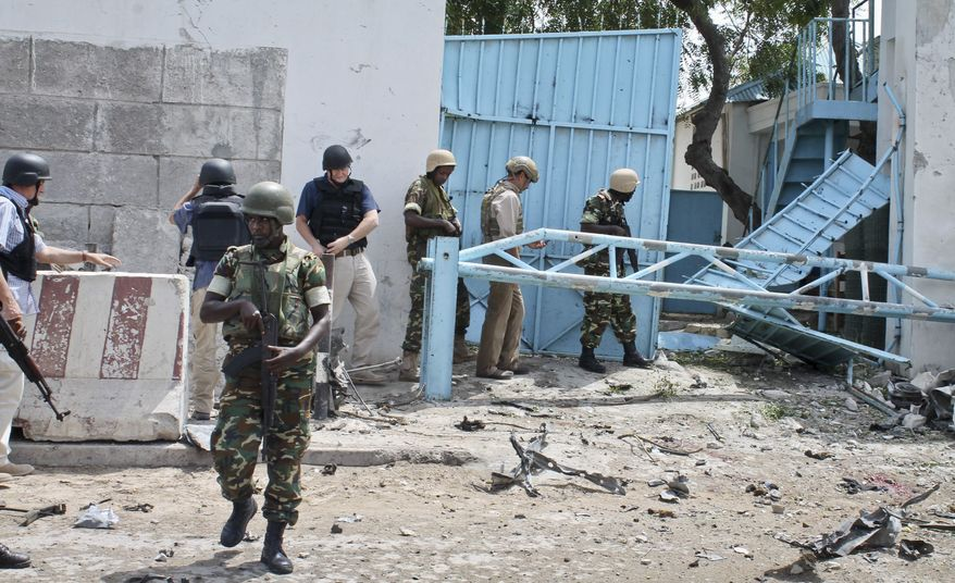 African Union peacekeepers and unidentified foreigners stand outside the main U.N. compound following an attack in Mogadishu, Somalia, on Wednesday, June 19, 2013. Al-Qaeda-linked militants detonated multiple bomb blasts and engaged in ongoing battles with security forces in an attempt to breach the compound in the Somali capital, officials said Wednesday. (AP Photo/Farah Abdi Warsameh)