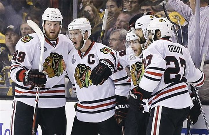 Chicago Blackhawks right wing Patrick Kane, second from right, celebrates his goal against the Boston Bruins with teammates during the second period in Game 4 of the NHL hockey Stanley Cup Finals, Wednesday, June 19, 2013, in Boston. (AP Photo/Elise Amendola)