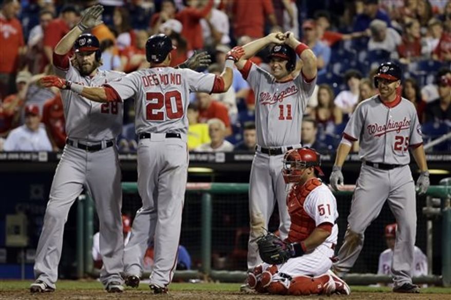 Washington Nationals' Ian Desmond (20) celebrates with Jayson Werth (28), Ryan Zimmerman (11) and Adam LaRoche (25) after Desmond's go-ahead grand slam off Philadelphia Phillies relief pitcher Michael Stutes in the 11th inning of a baseball game, Wednesday, June 19, 2013, in Philadelphia. Washington won 6-2 in 11 innings. At lower right is Carlos Ruiz. (AP Photo/Matt Slocum)