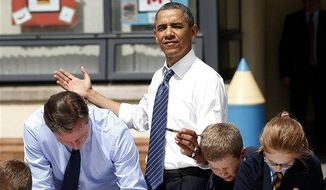 President Obama helps students as they work on a school project about the G-8 summit during a visit to the Enniskillen Integrated Primary School in Enniskillen, Northern Ireland, Monday, June 17, 2013. (Associated Press)