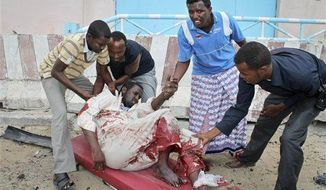 Somalis carry a man who was wounded during an attack on the U.N. compound in Mogadishu, Somalia Wednesday, June 19, 2013. (AP Photo/Farah Abdi Warsameh)